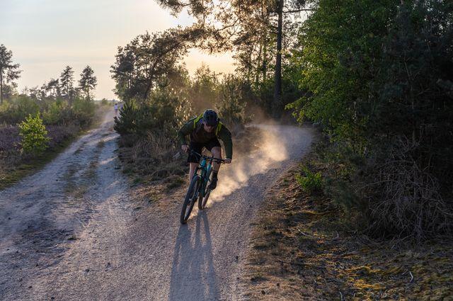 mountainbiker in de schemering met stofwolk