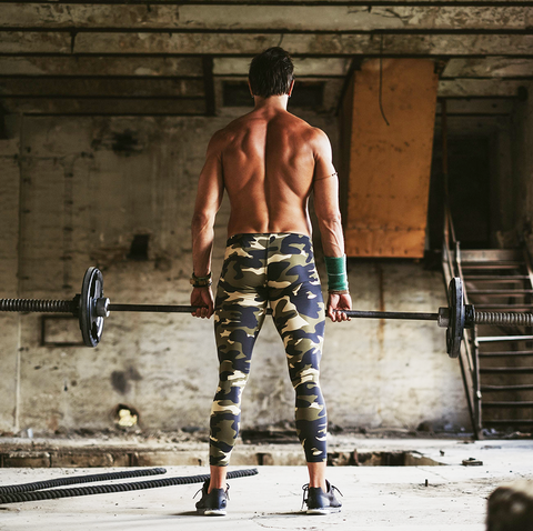 Shirtless man deadlifts in deserted building