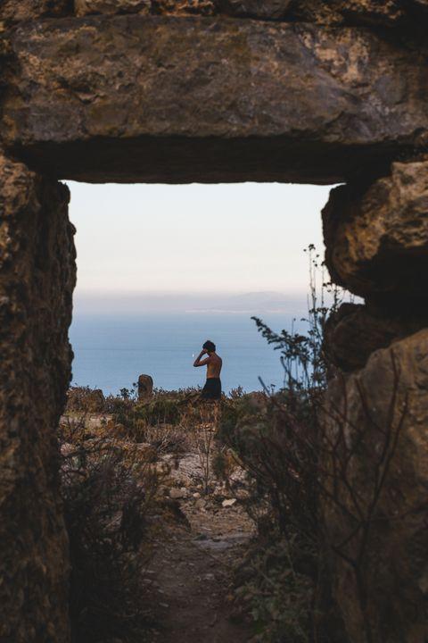 shirtless man standing on rock