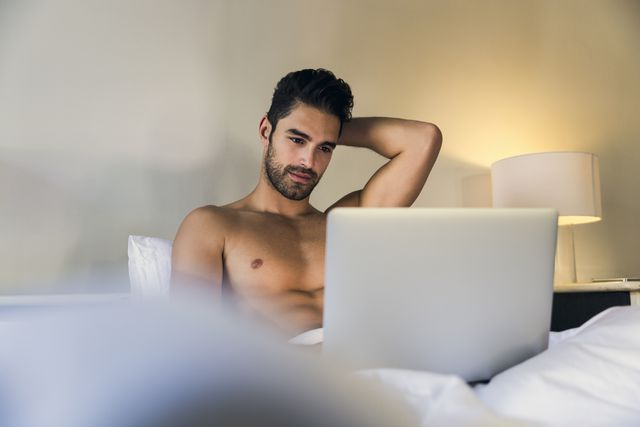 shirtless young man using laptop in bed