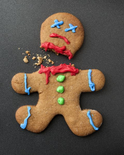 A shocked gingerbread man with broken leg next to a decapitated gingerbread man
