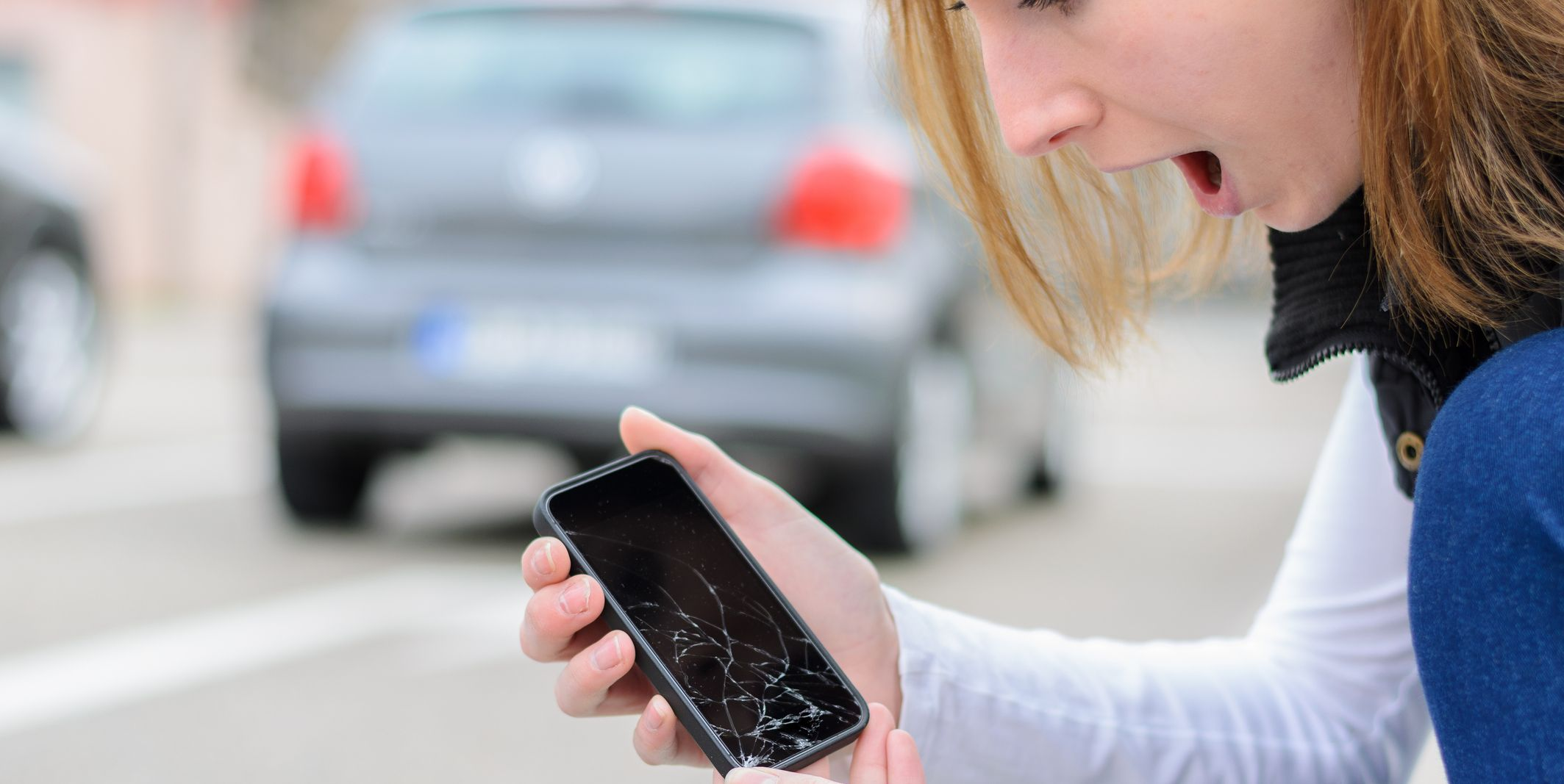 Shocked Woman Holding Mobile Phone with Broken Display