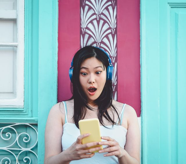 shocked woman using mobile phone while listening music against wall