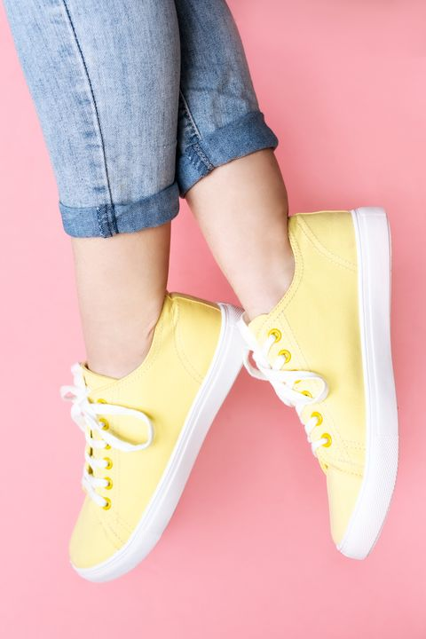 woman in stylish sneakers near color wall, closeup space for text