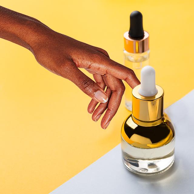 woman's hand touching a bottle of skin serum