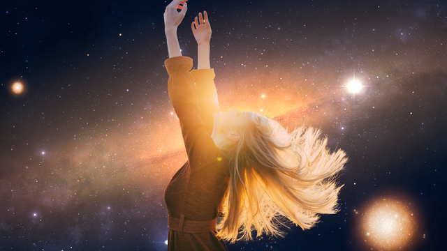 woman with hands up to the sky stars in the background