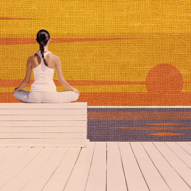 woman meditating in front of a sunset