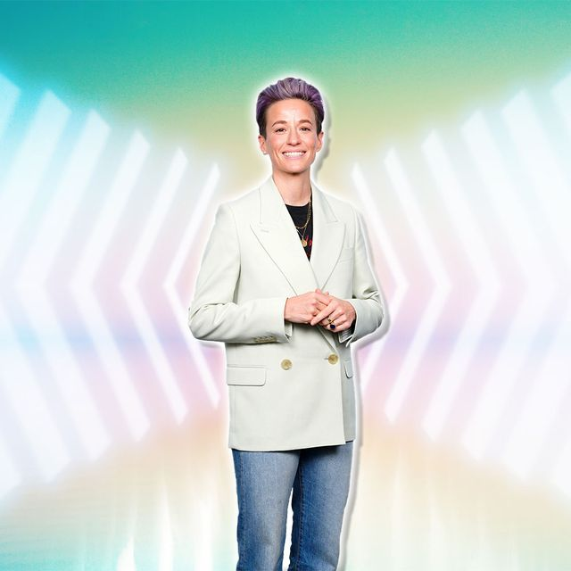 megan rapinoe poses in a white blazer and jeans against a colorful backdrop