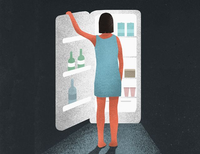 a woman standing in front of refrigerator staring at food at night