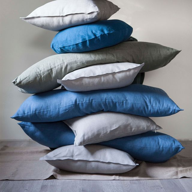 high pile of blue and grey pillows stacked on top of each other