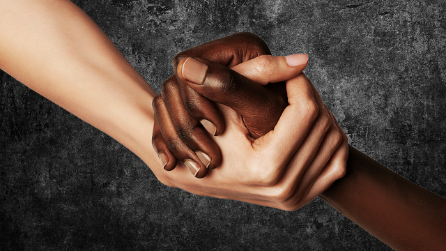 a black and white hand holding each other