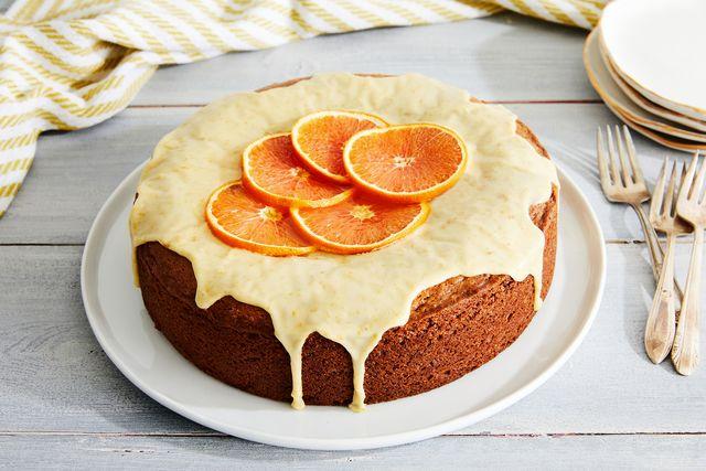 orange cake covered in orange icing with thin slices of oranges