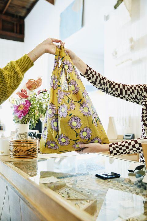 shop owner handing reusable bag to client in boutique