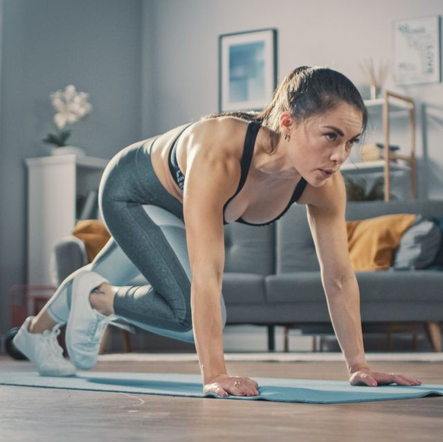 shot of a beautiful confident strong fitness female in a grey athletic outfit is doing mountain climber exercises in her bright and spacious apartment with cozy minimalistic interior