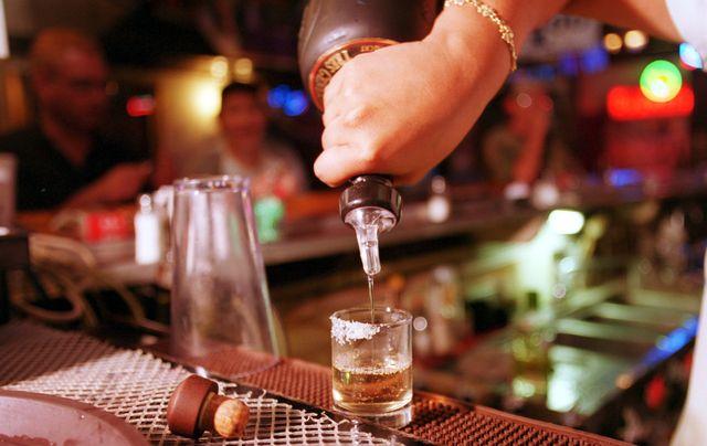 un camarero sirve un chupito de tequila