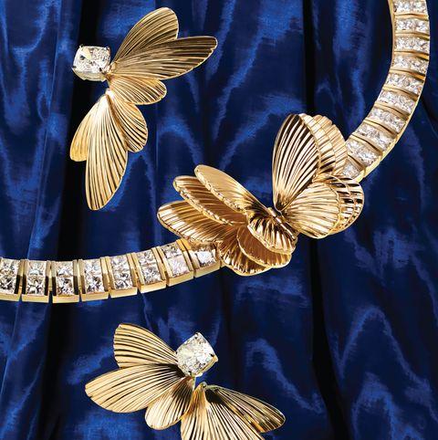gold earrings and collar against blue velvet background