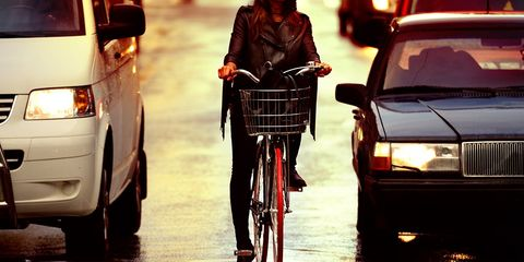 A cyclist between two cars.