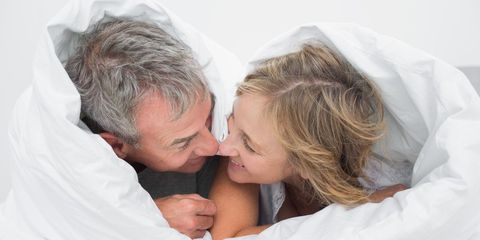 Happy older couple laying in bed