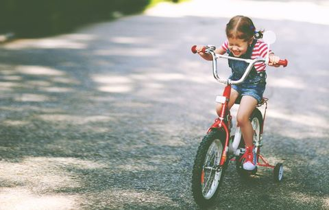 young girl riding bike happily