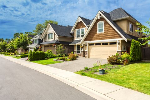 nicely trimmed and manicured garden in front of a luxury house on a sunny summer day street of houses in the suburbs of canada, home improvement   bbm 6 back cover ad