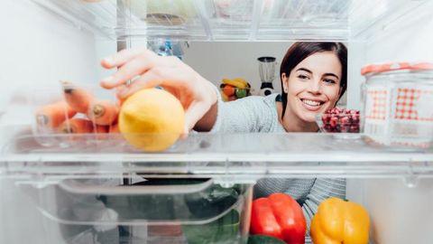 Vrouw pakt een citroen uit de koelkast