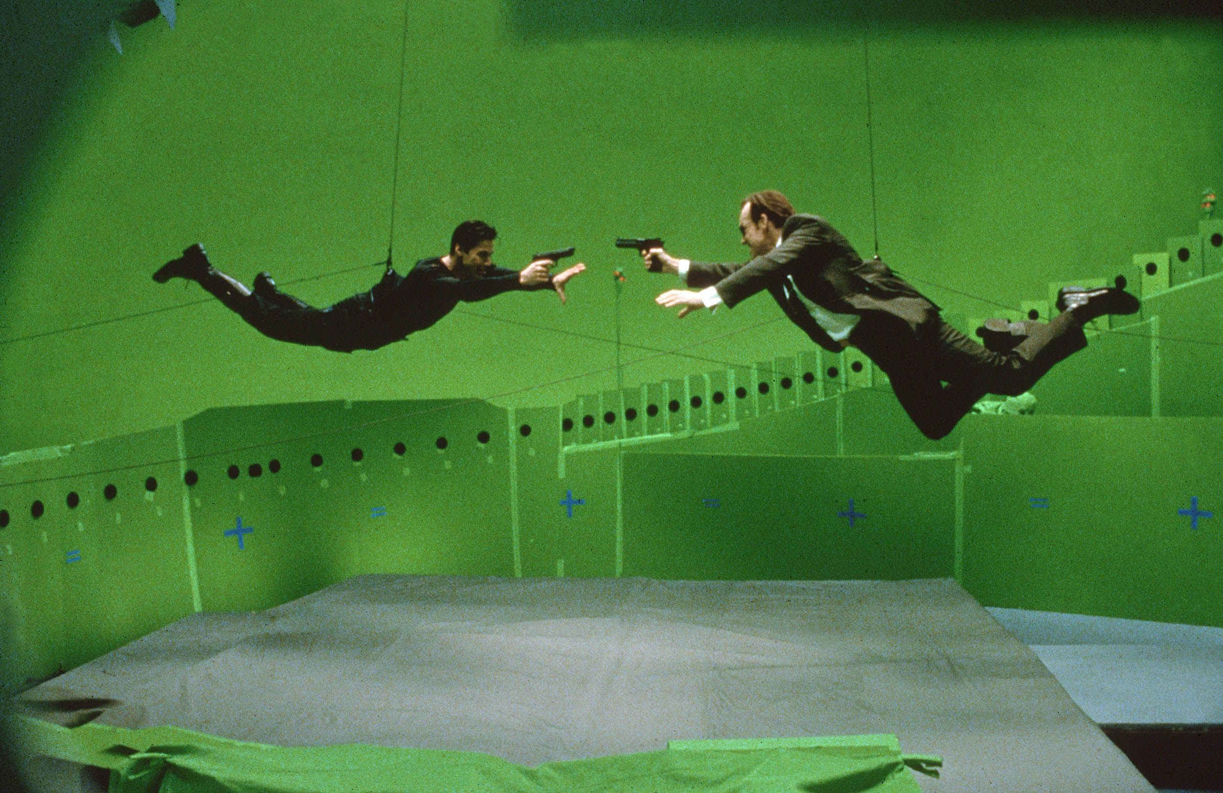 Keanu Reeves and Hugo Weaving filming in front of a green screen for the 1999 film The Matrix.