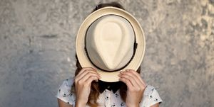 shy woman hiding behind hat
