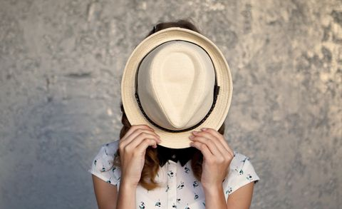 shy woman hiding behind hat