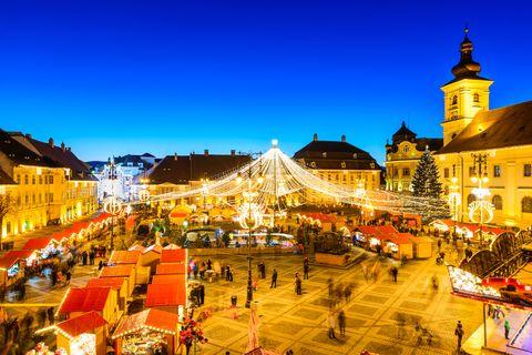 sibiu, romania   20 december 2014 night image with tourists at christmas market in great market of medieval sibiu, transylvania landmark
