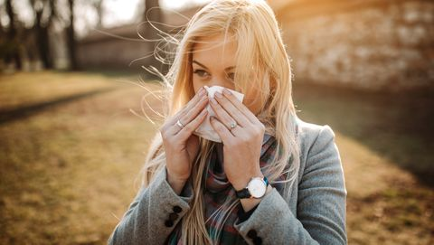 Sick blonde blowing her nose