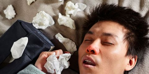 Sick Guy in Bed With Box of Tissues