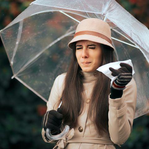 sick woman holding  umbrella in autumn rain suffering from allergies