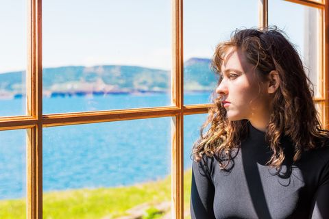 side closeup portrait of one, lonely, alone young woman face by large glass window looking at peaceful ocean view, cliff, in rustic wooden house