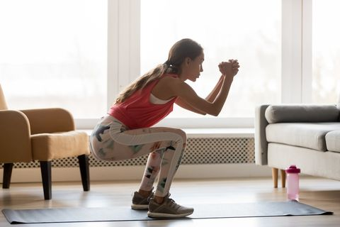 side full length view woman wearing activewear makes deep squat
