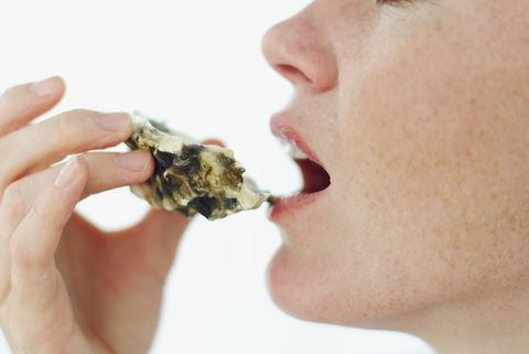 side profile of a young woman eating an oyster from the shell