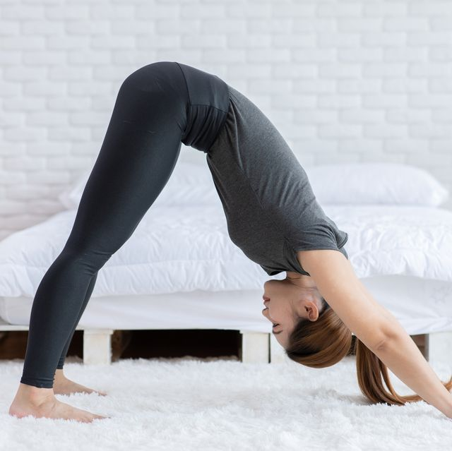 side view full length of woman exercising in bedroom at home