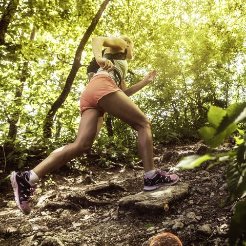 side view of a woman running uphill in a forest