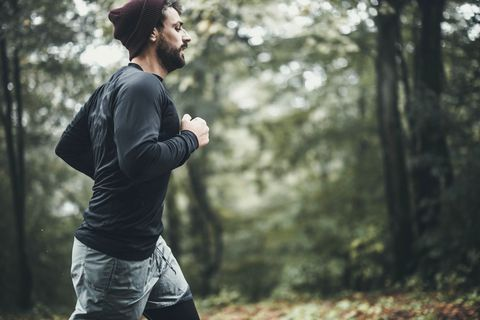 side view of athletic man running in autumn day at the park