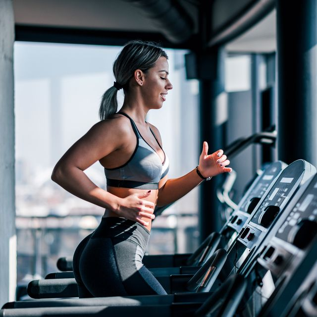 side view of beautiful muscular woman running on treadmill