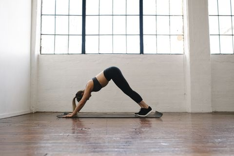 Side view of female athlete practicing downward facing dog position in gym