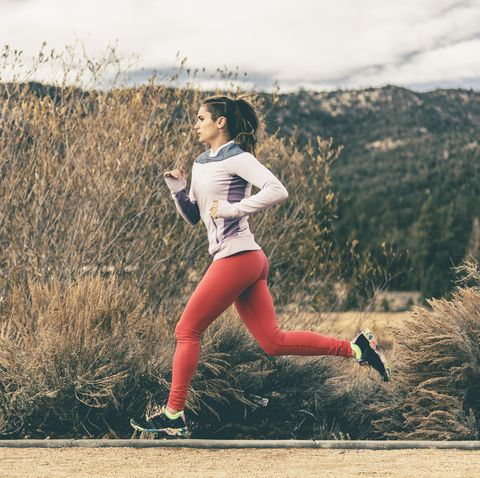 side view of female athlete running by field