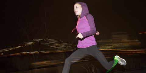 Side view of female jogger wearing hood while running on field at night
