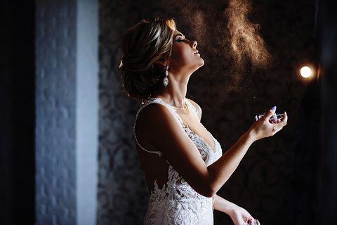 side view of female model spraying perfume in darkroom
