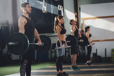 Side view of male and female athletes lifting barbells at health club