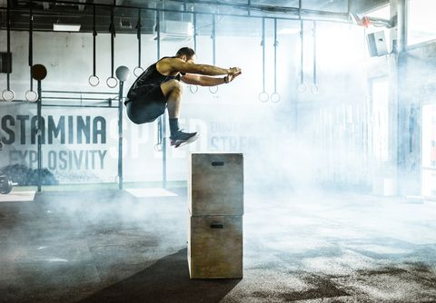 Side view of male athlete jumping on crate during sport training in a gym.