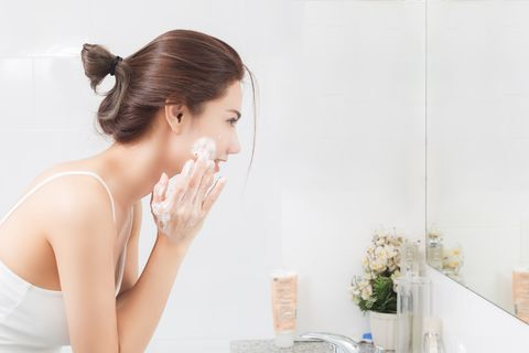 side view of mid adult woman washing face while looking in mirror at home
