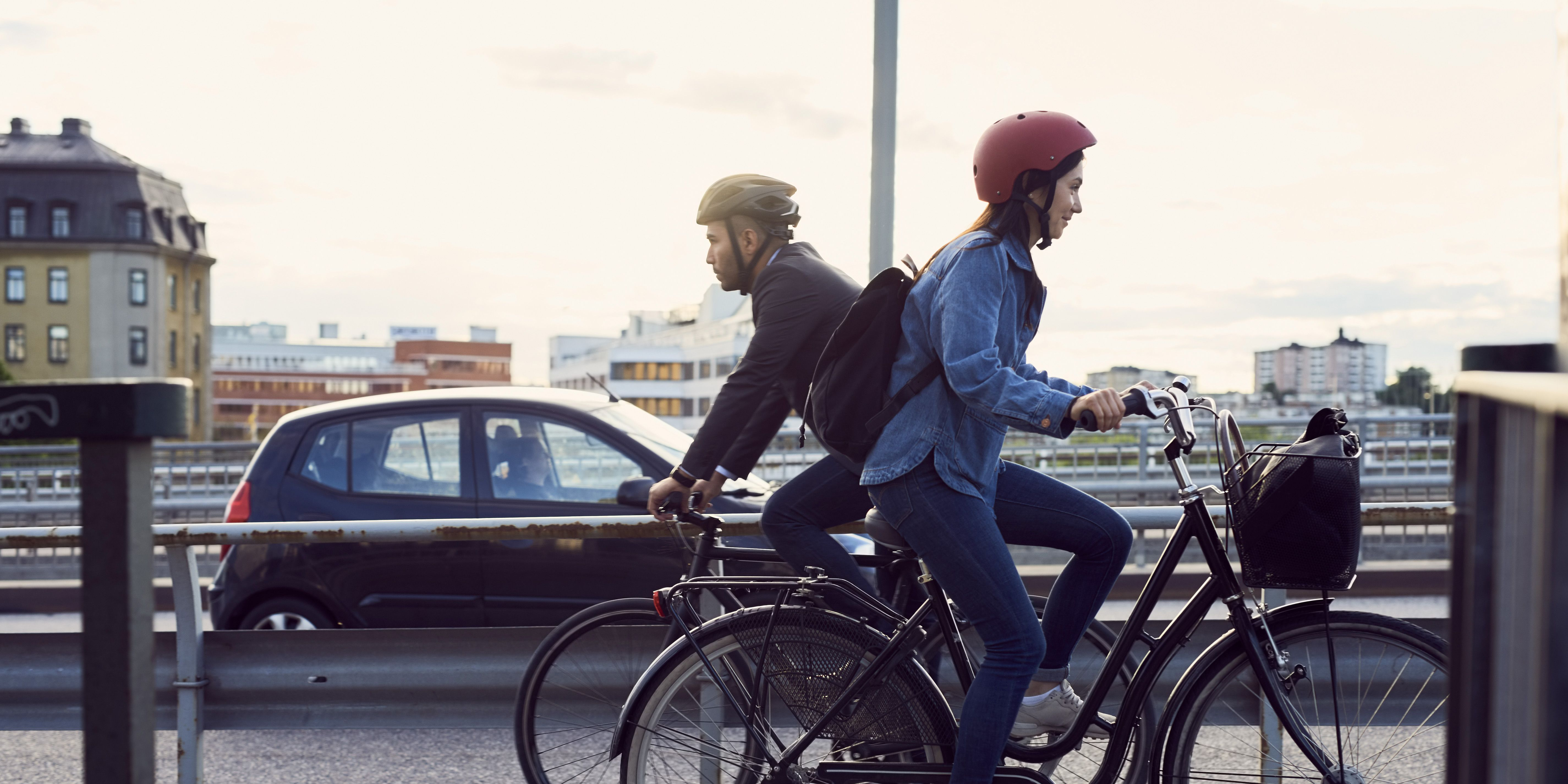 Side view of people cycling on street against sky