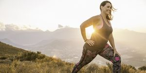 Side view of plus size woman wearing sports clothing on mountain, lunging at sunrise