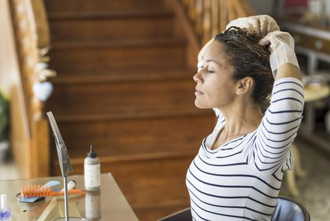 side view of woman dying hair at home