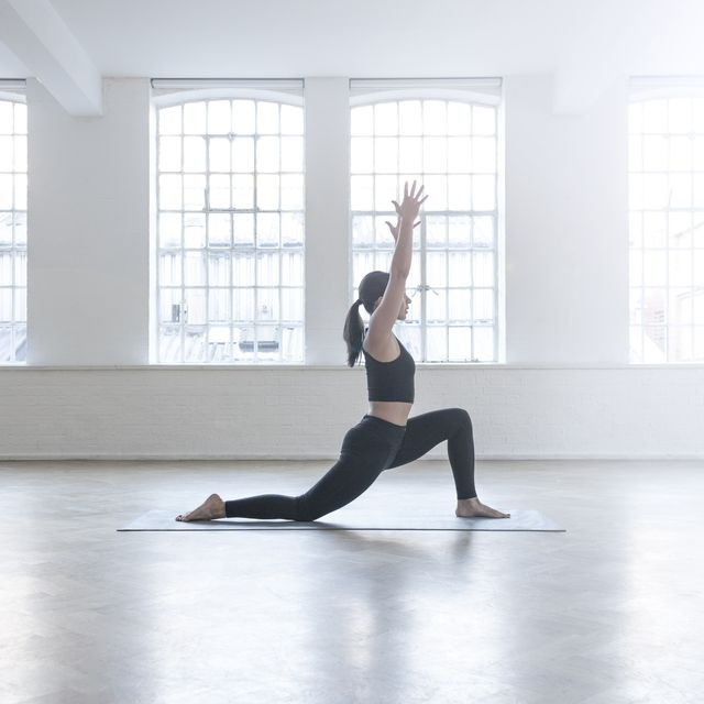 Side view of woman in dance studio in yoga position
